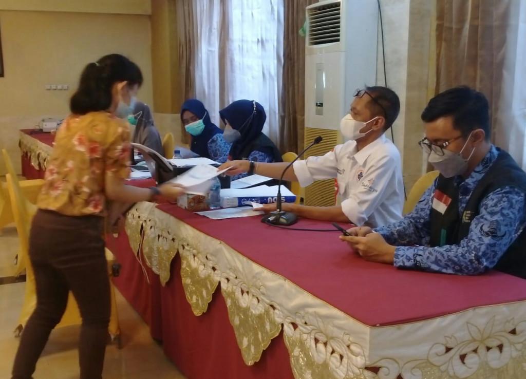 Teks Foto : Setelah divaksin Covid-19 oleh petugas dari Dinas Kesehatan Kab. Sidoarjo,  pekerja hotel dan restoran di Sidoarjo  menerima sertifikat  telah melakukan vaksinasi Covid-19 dua kali